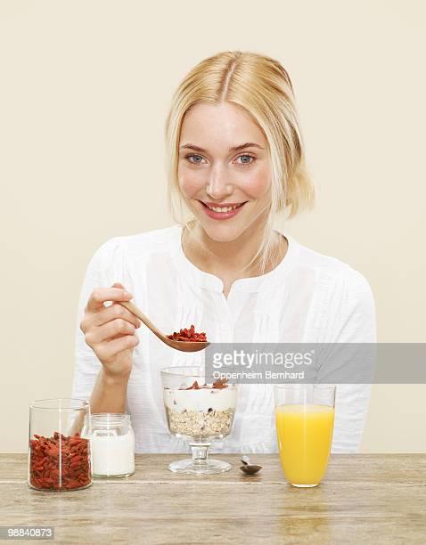 female sprinkling goji berries over her breakfast