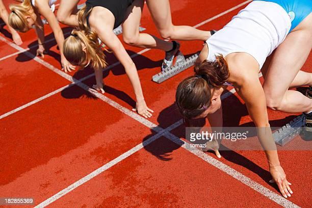 Female sprinters in starting blocks