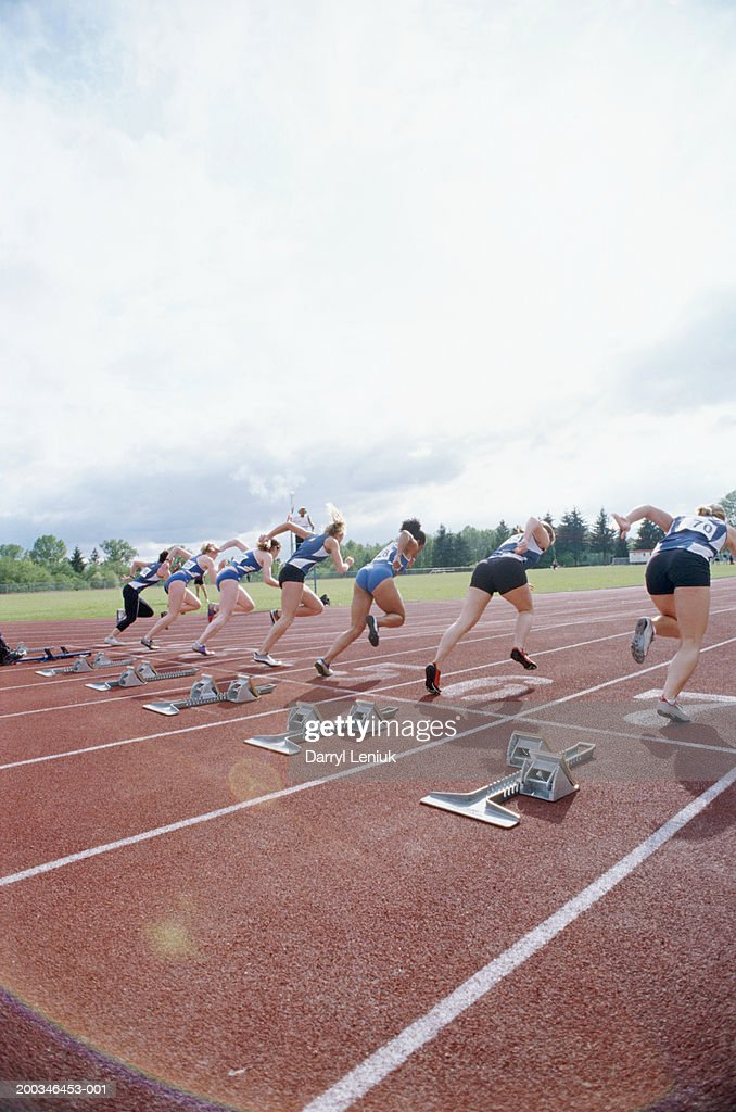 Female sprinters on track, rear view : Stock Photo