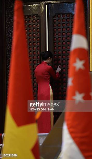 A female staff in traditional 'Ao Dai' dress peeks into a meeting room where visiting Singaporean Prime Minister Lee Hsien Loong and his Vietnamese...