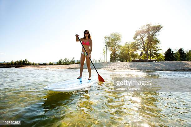 A female stand up paddling.