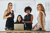 Group of multiracial businesswomen in casuals together at office desk and looking at camera. Female startup business team portrait.