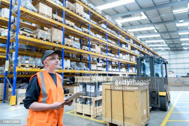 Female storage worker in train works warehouse