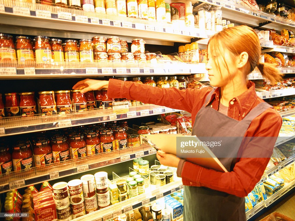 Female store attendant in grocery store, stock taking : Stock Photo