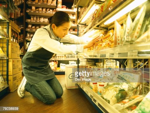 Female store attendant packing grocery : Stock Photo