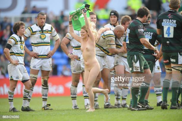 A female streaker runs infront of the Northampton Saints' players during the game
