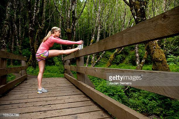 A female stretching on a wooden bridge.