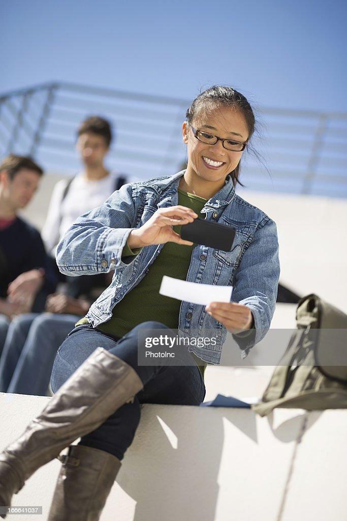 Female Student Depositing Check Through Phone