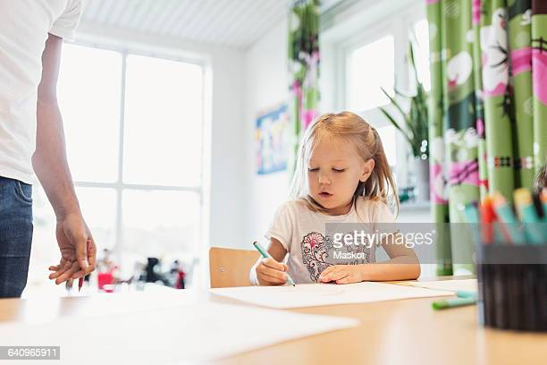 Female student drawing at table in classroom