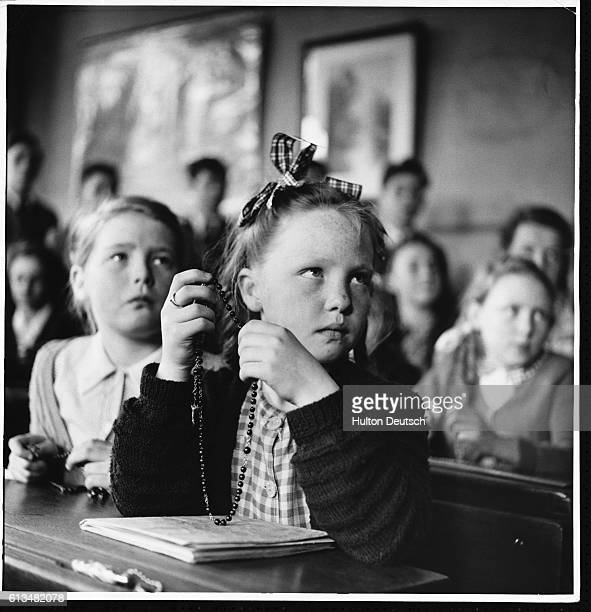 A female student from Langley Park holds her rosary beads after a visit to her school from Father Patrick Peyton who is on a crusade to restore...