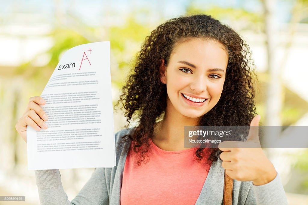 Studentin Gestikulieren Daumen nach oben und hältst eine Untersuchung Ergebnis : Stock-Foto