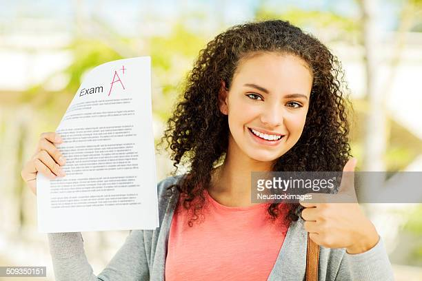 Female Student Gesturing Thumbs Up While Holding A Exam Result