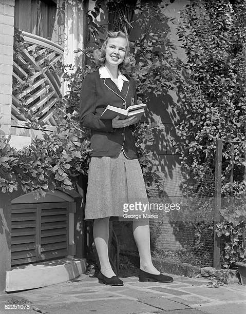 Female student holding book in back yard, portrait
