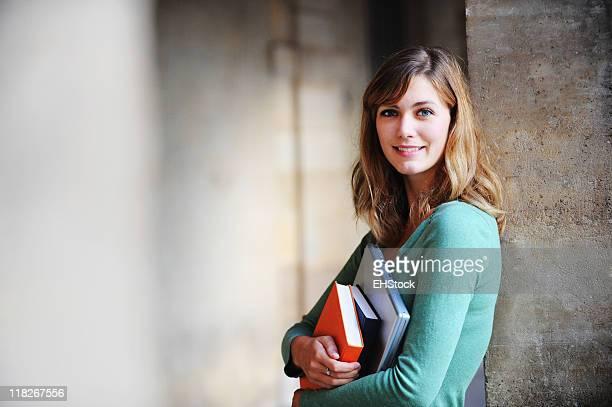 Studentin hält Bücher und laptop