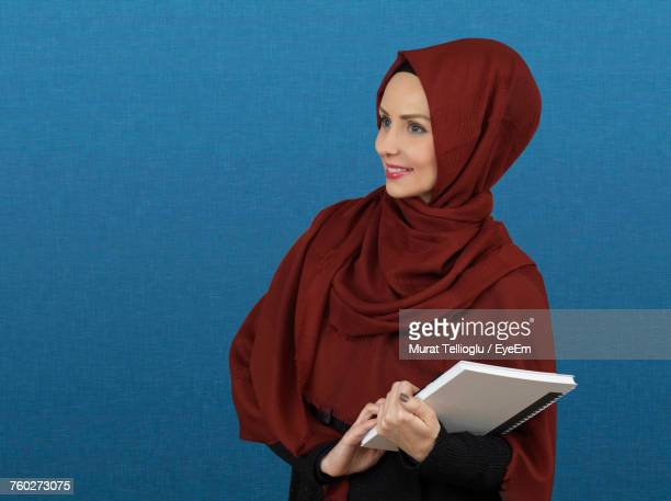 Female Student In Hijab Holding Book While Standing By Blue Wall