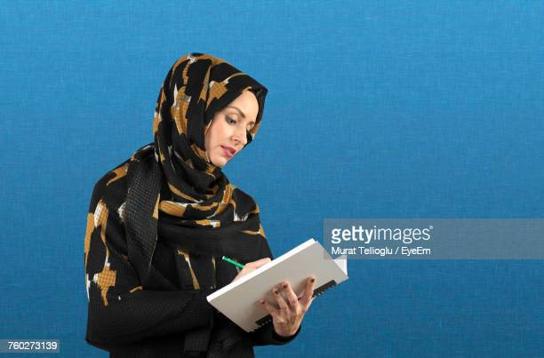 Female Student In Hijab Writing On Book While Standing By Blue Wall