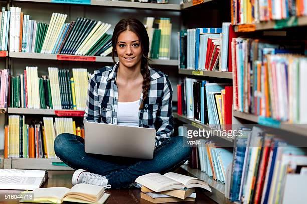 Mulher estudante na biblioteca com computador portátil