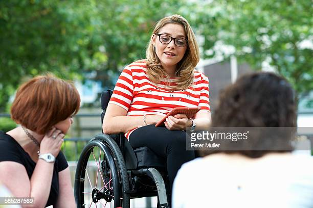 Female student in wheelchair chatting to friends on college campus