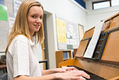 Female student learning piano in classroom