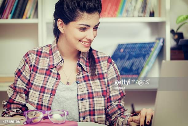 Studentin lernt zu Hause mit einem Laptop