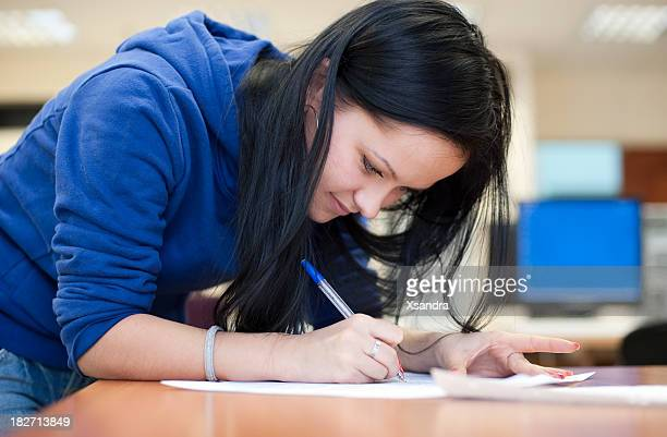 Female student making notes on piece of paper