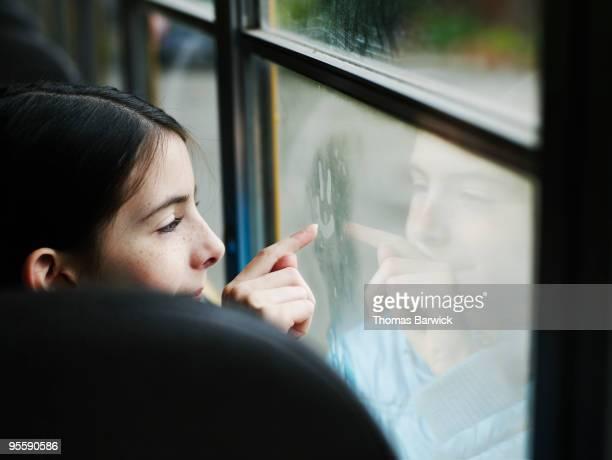 Female student on school bus drawing on window