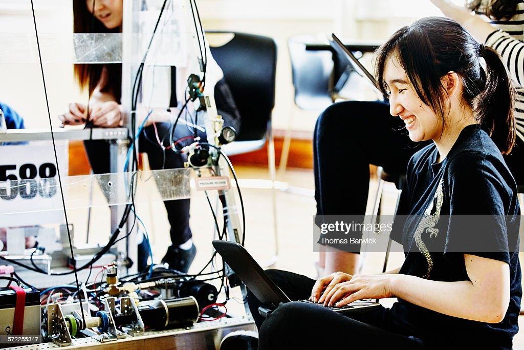 Female student programing robot with laptop : Stock Photo