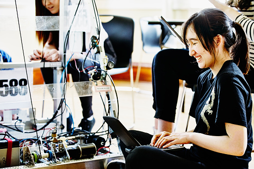 Female student programing robot with laptop
