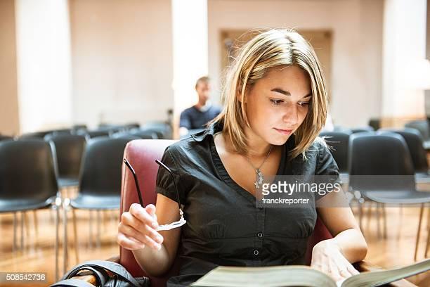 Weibliche Schüler lesen ein Buch in der Bibliothek