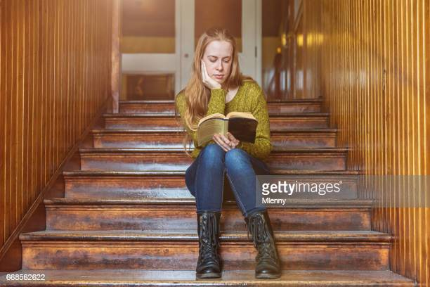Female student reading book on wooden academy staircase