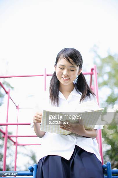 Female student reading book sitting on jungle gym