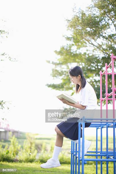 Female student reading book sitting on jungle gym, side view