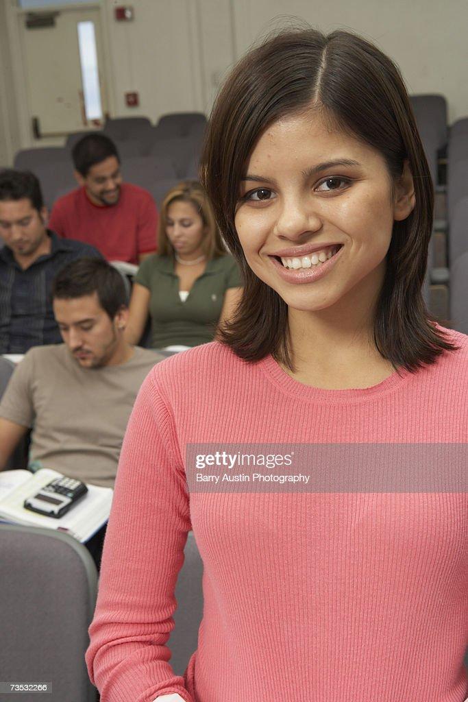 Female student smiling in lecture theatre, portrait : Stock Photo