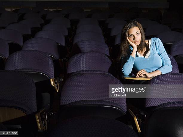 Female student taking notes in lecture hall