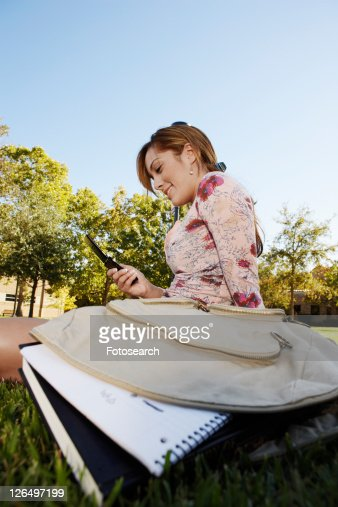 Female student text messaging on lawn (low angle view)