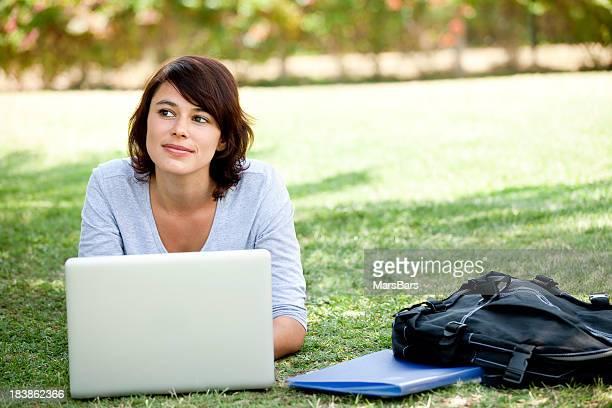 Female student thinking while using laptop