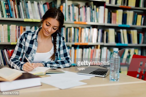 Female student using laptop for taking notes to study.
