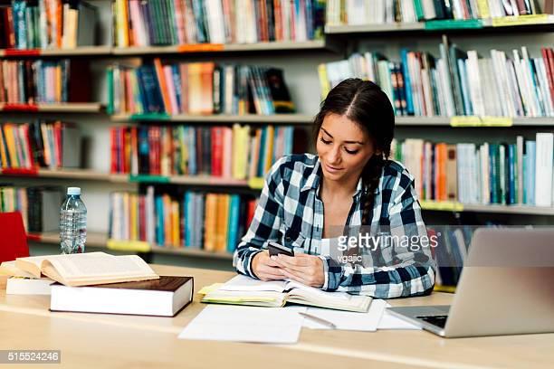 Studentessa utilizzando smartphone in biblioteca