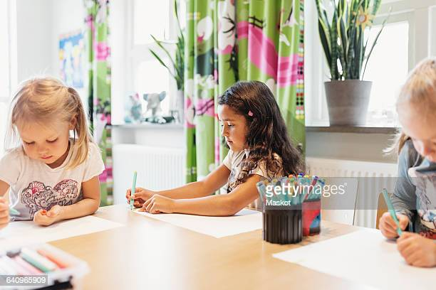 Female students drawing at table in classroom