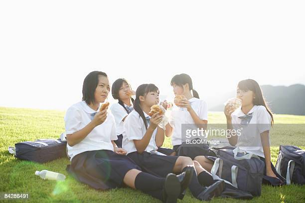 Female students having lunch sitting on grass