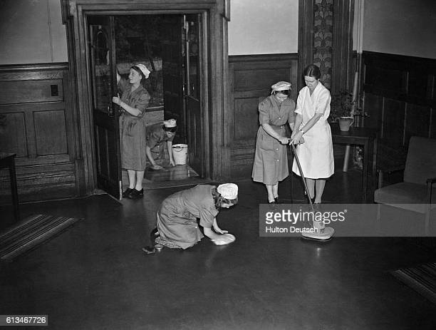 Female students learn to polish floors by hand and by machine as part of their government training course run by the National Institute of...