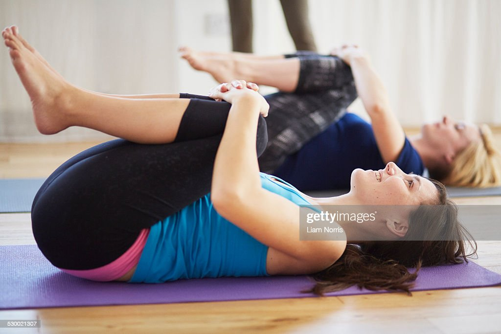 Female students lying on back hugging knees in pilates class