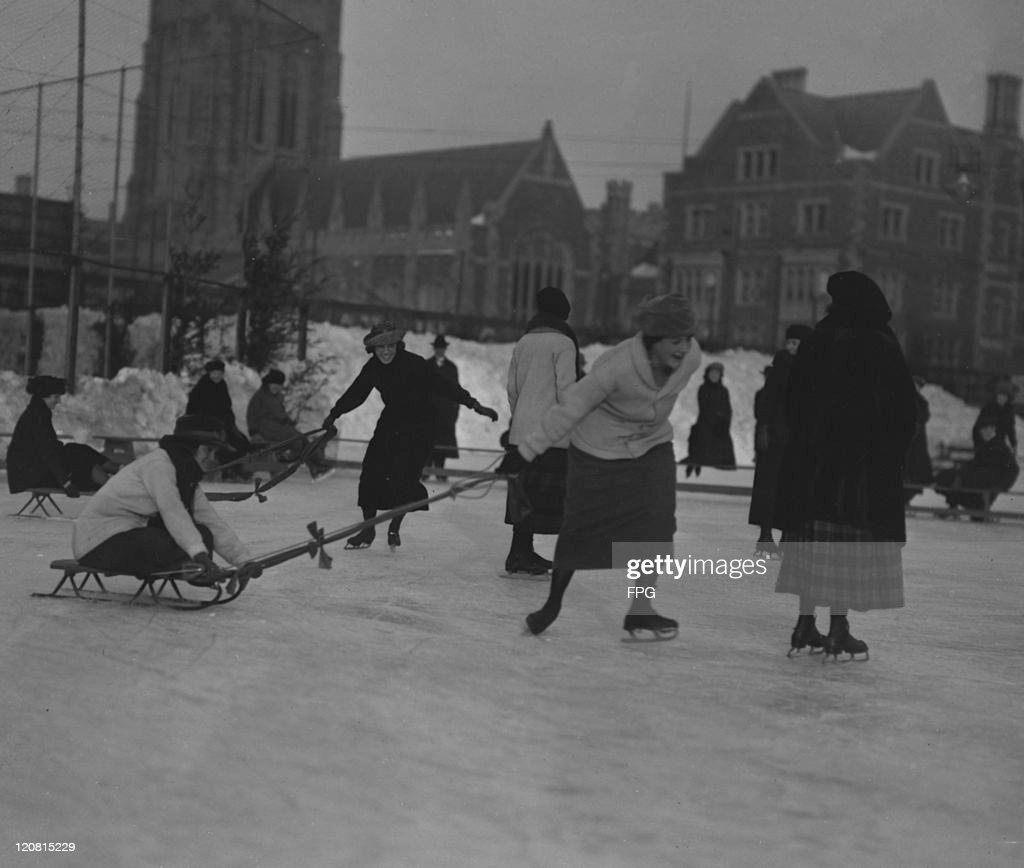 Female students skating and tobogganing on a frozen pond at Barnard College Manhattan New York City circa 1920