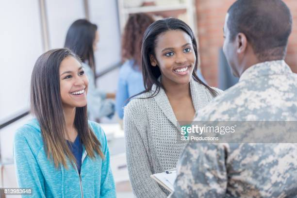 Female students talk with recruitment officer