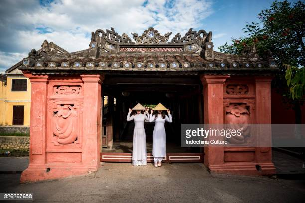 Female students wearing Vietnamese Ao Dai at Japanese Covered Bridge, Hoi An, Vietnam