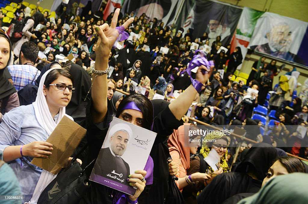 A female supporter of Hassan Rowhani, one of the eight candidates approved to run for the Iranian presidency wears purple wrist band which is the color of his campaign while holding his picture during a campaign rally in Shiroudi stadium on June 8, 2013 in Tehran, Iran. Iran is to go to the polls for the Iranian general election on June 14, 2013.