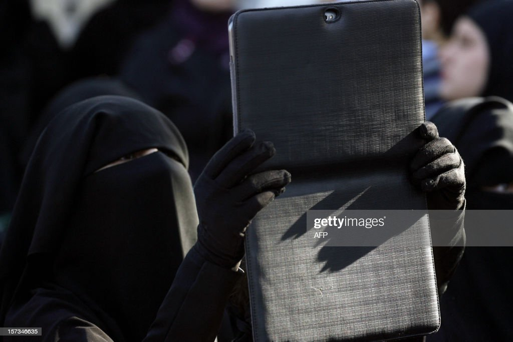 A female supporter of Lebanese Salafist figure, Sheikh Ahmad al-Assir, takes a picture with her tablet during a protest against the Syrian regime in the southern Lebanese city of Sidon on December 2, 2012.
