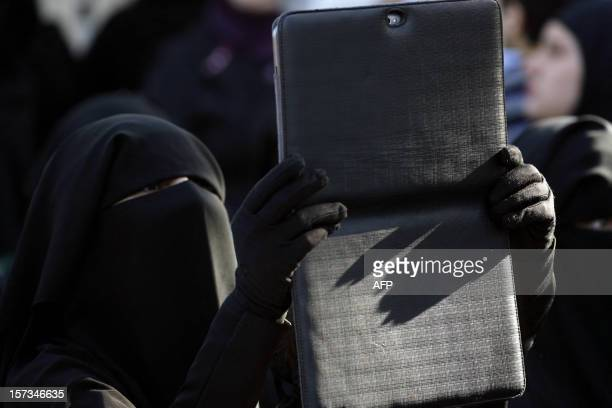 A female supporter of Lebanese Salafist figure Sheikh Ahmad alAssir takes a picture with her tablet during a protest against the Syrian regime in the...
