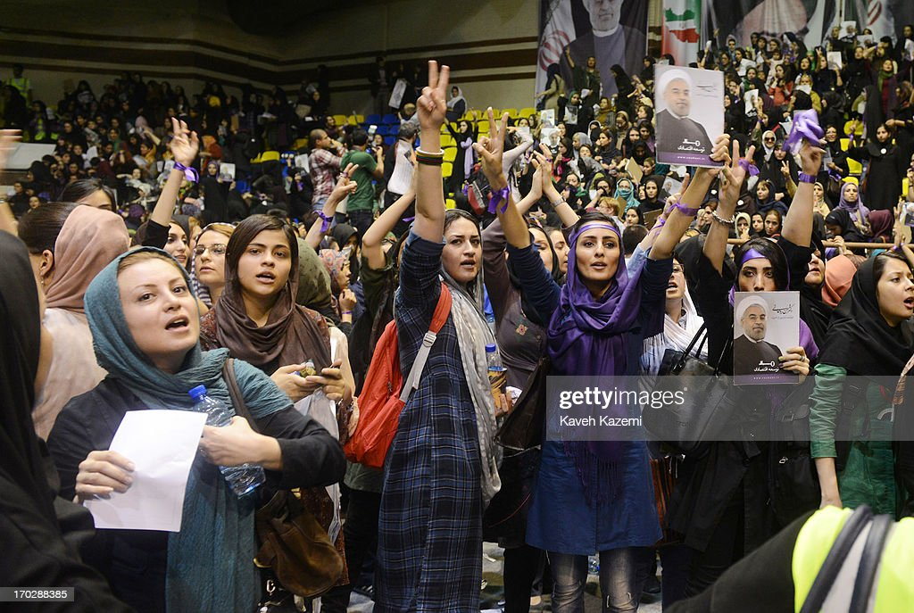 Female supporters of Hassan Rowhani, one of the eight candidates approved to run for the Iranian presidency wear purple wrist bands which is the color of his campaign show victory signs while holding his pictures during a campaign rally in Shiroudi stadium on June 8, 2013 in Tehran, Iran. Iran is to go to the polls for the Iranian general election on June 14, 2013.