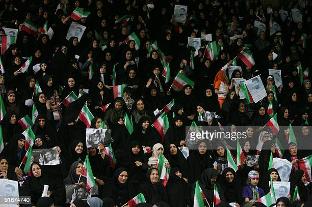 Female supporters of Iranian President Mahmoud Ahmadinejad wave national flags as they listen to his speech during an electoral campaign meeting in...